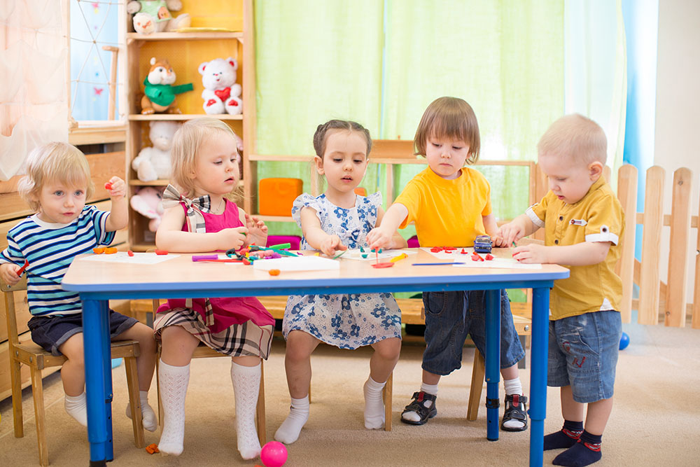kids group learning arts and crafts in day care center playroom at a Preschool & Daycare Serving Frisco, TX