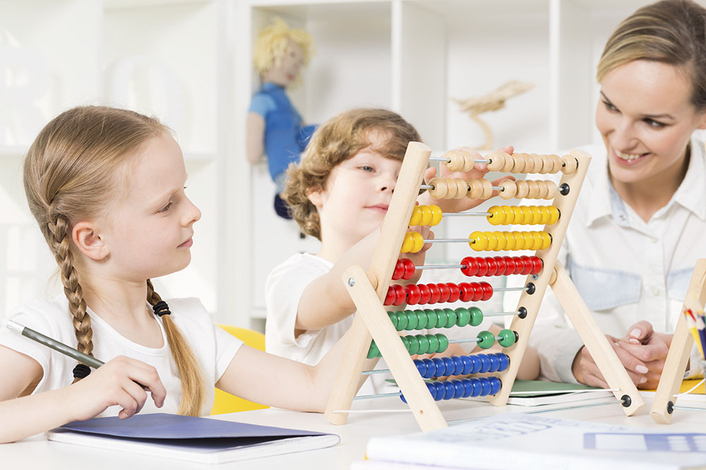 Children in elementary school learning to count on a colorful abacus with the help of their teacher at a Preschool & Daycare Serving Frisco, TX