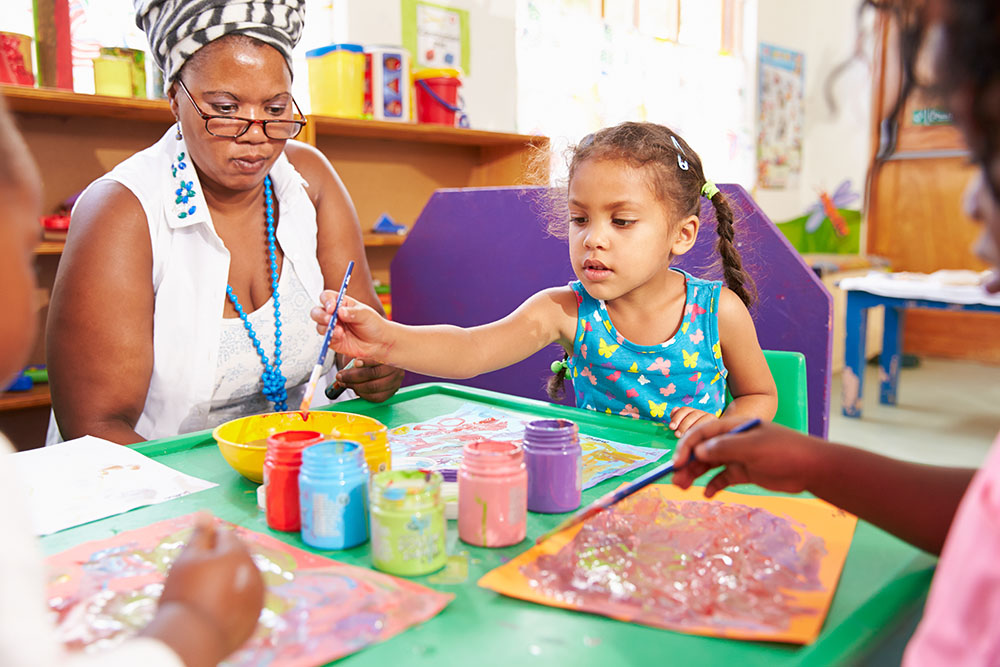 Teacher sitting with kids in a preschool class, close up doing paintings at a Preschool & Daycare Serving Frisco, TX