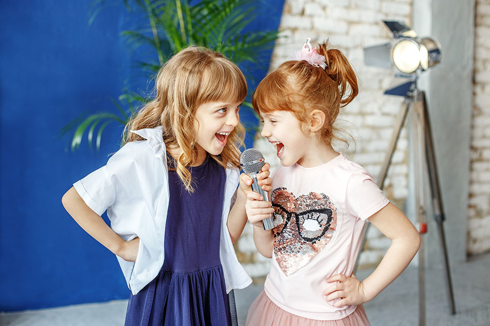 Two happy little children sing a song in karaoke. The concept is childhood, lifestyle, music, singing, friendship at a Preschool & Daycare Serving Frisco, TX
