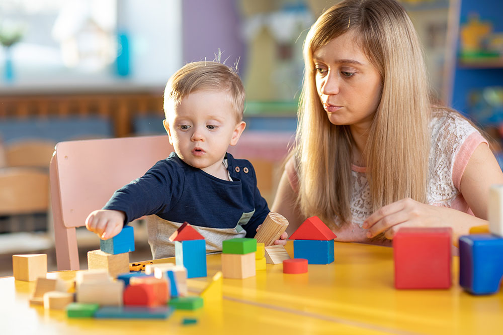 Cute female teacher and child toddler boy playing educational toys in kindergarten or nursery at a Preschool & Daycare Serving Frisco, TX