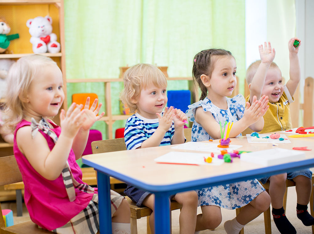 Group of kids learning arts and crafts in day care center or kindergarten, happy and clapping at a Preschool & Daycare Serving Frisco, TX