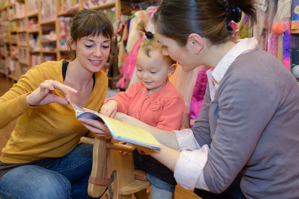 mother and daughter with attractive vendor in toy store at a Preschool & Daycare Serving Frisco, TX