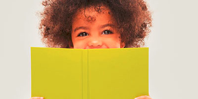 Happy preschool girl smiling while reading a book at a Preschool & Daycare Serving Frisco, TX