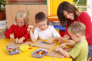teacher and three preschoolers playing with wooden blocks , educational toys, at a Preschool & Daycare Serving Frisco, TX
