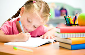 young little kid girl enjoy writing in classroom at a Preschool & Daycare Serving Frisco, TX