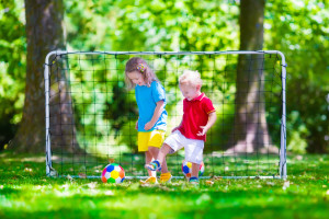 Two happy children playing European football outdoors in school yard. Kids play soccer. Active sport for preschool child. Ball game for young kid team. Boy and girl score a goal in football match at a Preschool & Daycare Serving Frisco, TX