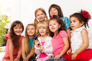 group of happy little kids, boys and girls, singing together on a microphone , working together, at a Preschool & Daycare Serving Frisco, TX