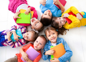 Kids holding colorful notebooks while lying around in circles at a Preschool & Daycare Serving Frisco, TX