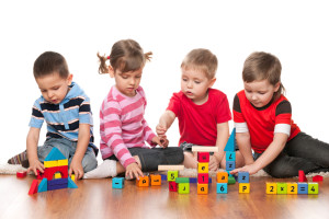 Four kids are playing on the floor with educational blocks with letters at a Preschool & Daycare Serving Frisco, TX