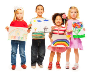 Three happy girls and boy Caucasian and holding pictures they draw ,art activity at school at a Preschool & Daycare Serving Frisco, TX
