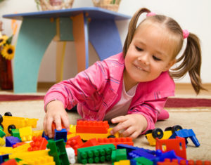 Little girl is playing with building bricks in preschool while laying on floor at a Preschool & Daycare Serving Frisco, TX
