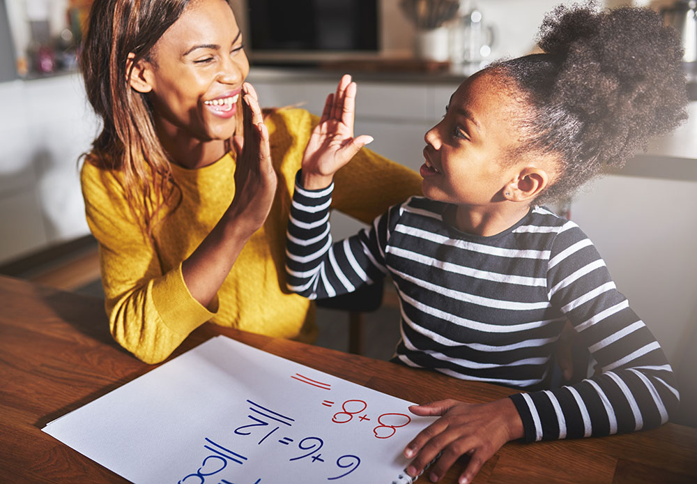 Learning to calculate, high five success, african american mother and child, teaming up, at a Preschool & Daycare Serving Frisco, TX