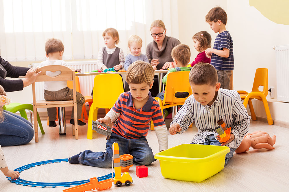 Two cute little boys playing with toy railway in kindergarten with children and teacher at the background at a Preschool & Daycare Serving Frisco, TX